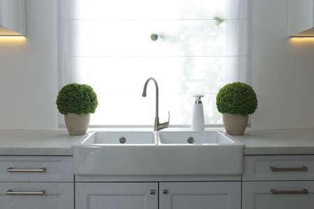 Modern double bowl sink near window in kitchen