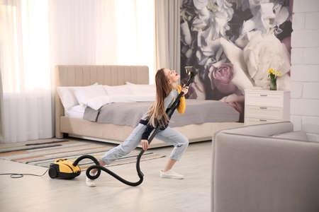 Young woman having fun while vacuuming at home Imagens