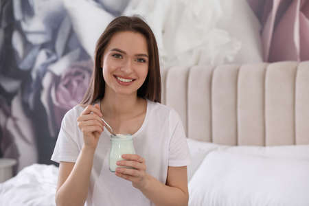 Young attractive woman with tasty yogurt on bed at home