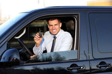 Man with key sitting in car outdoors. Buying new auto