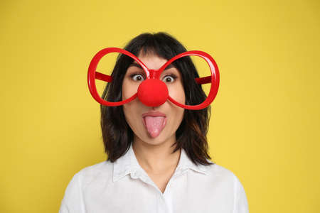 Funny woman with clown nose and large glasses on yellow background. April fool's day