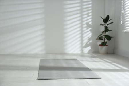 Unrolled grey yoga mat on floor in room. Space for text