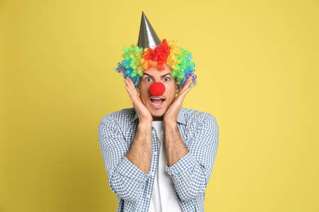 Funny man with clown nose, party hat and rainbow wig on yellow background. April fool's day