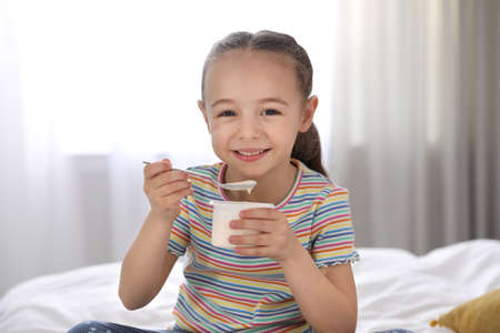 Cute little girl eating tasty yogurt on bed at home