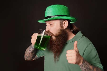 Bearded man drinking green beer on black background. St. Patricks Day celebration
