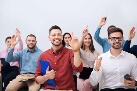 People raising hands to ask questions at business training on white background