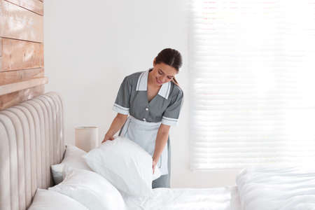 Young chambermaid making bed in hotel room Imagens