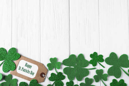 Flat lay composition with clover leaves on white wooden table, space for text. St. Patrick's Day celebration