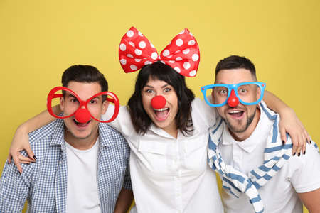 Group of friends with funny accessories on yellow background. April fool's day