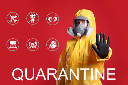 Woman in chemical protective suit showing stop gesture against red background. Hold on quarantine rules during coronavirus outbreak
