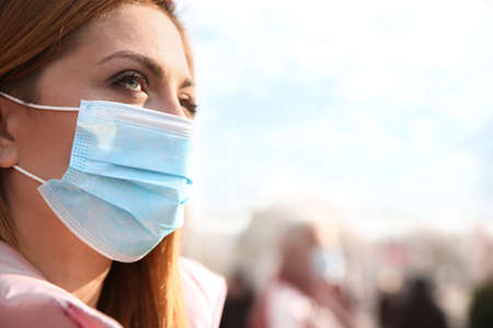 Woman with medical mask on city street. Virus protection