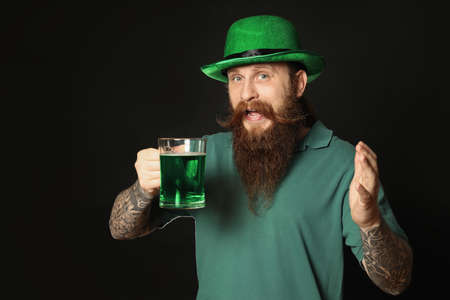 Bearded man with green beer on black background. St. Patricks Day celebration