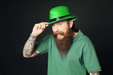 Bearded man in green hat on black background. St. Patricks Day celebration