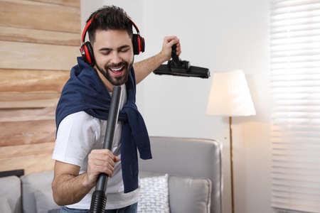 Young man having fun while vacuuming at home
