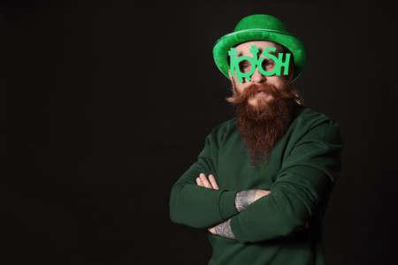 Bearded man in party glasses on black background. St. Patricks Day celebration