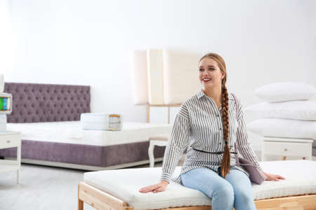 Young woman testing mattress in furniture store. Space for text