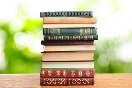 Collection of different books on wooden table against blurred green background Zdjęcie Seryjne