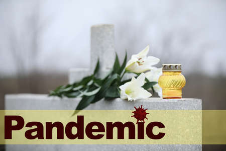 White lilies and candle on light grey granite tombstone outdoors. Outbreak of pandemic disease