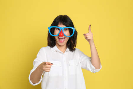Joyful woman with funny glasses on yellow background. April fool's day Banco de Imagens