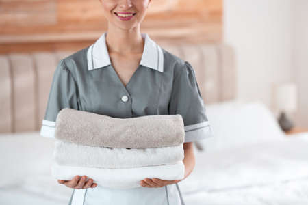 Young chambermaid holding stack of fresh towels in bedroom, closeup