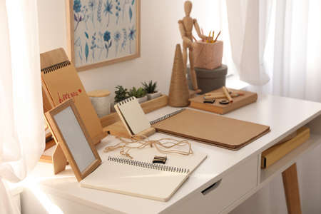 Wooden human figure and stationery on white table indoors. Interior elements Foto de archivo