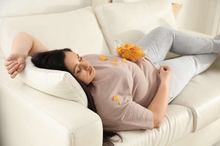 Lazy overweight woman with chips resting on sofa at home