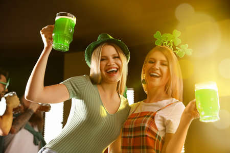 Young women with glasses of green beer in pub. St. Patrick's Day celebration Zdjęcie Seryjne - 143223864