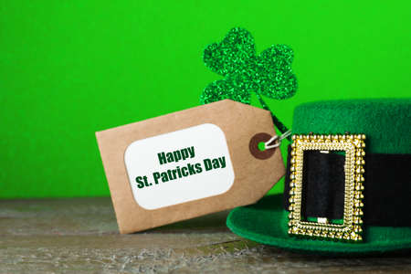 Green leprechaun hat, tag and clover leaf on wooden table against green background, closeup. St. Patricks Day celebration