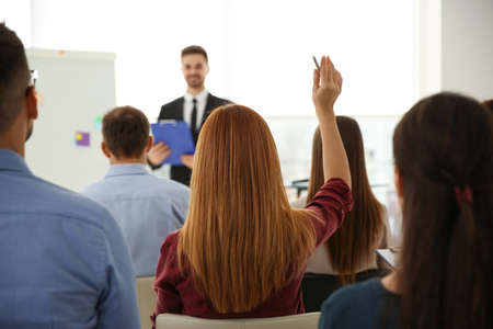Young woman raising hand to ask question at business training indoors, back view Stock Photo