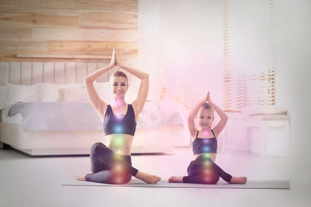 Mother and daughter with chakra points practicing yoga at home. Healing energy