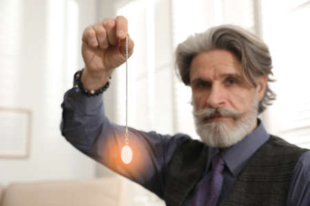 Psychotherapist with pendulum in office. Hypnotherapy session