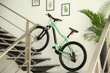 Modern green bicycle on stairs at home