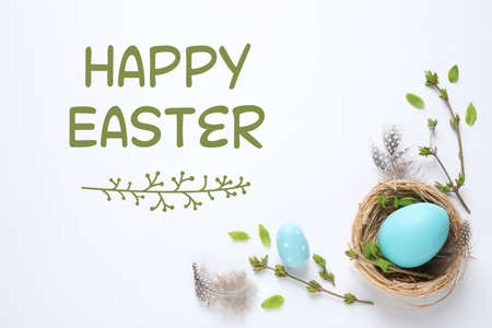 Flat lay composition with text Happy Easter and eggs on white background Stock Photo