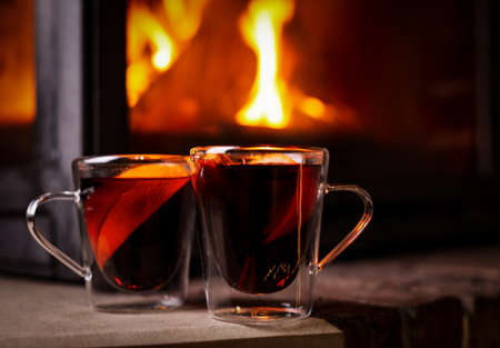 Tasty mulled wine in glass cups near fireplace indoors Stock Photo