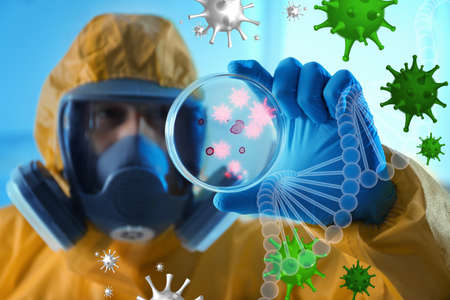 Scientist in chemical protective suit with Petri dish at laboratory, focus on hand. Virus research