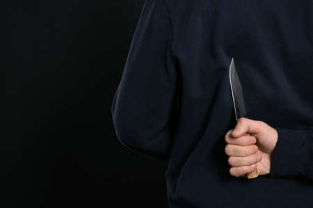 Man with knife behind his back on black background, closeup. Dangerous criminal