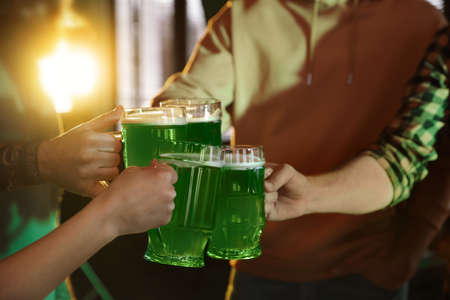 Group of friends toasting with green beer in pub, closeup. St. Patricks Day celebration Zdjęcie Seryjne