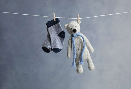 Pair of child's socks and toy bear hanging on laundry line against dark background