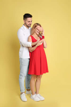 Man with engagement ring making marriage proposal to girlfriend on yellow background
