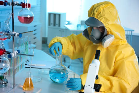 Scientist in chemical protective suit working at laboratory. Virus research