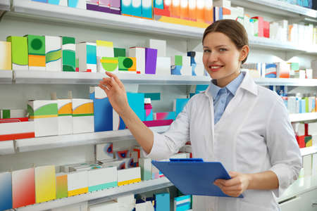 Professional pharmacist with clipboard in modern drugstore