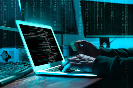 Cyber criminal with credit card hacking system at table, digital binary code on background Imagens