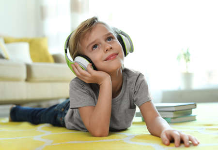Cute little boy with headphones listening to audiobook at home 写真素材