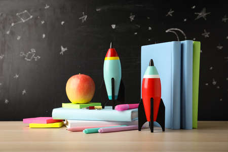 Bright toy rockets and school supplies on wooden table Standard-Bild - 143298536