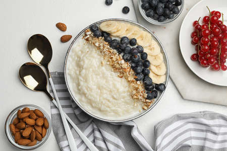 Delicious rice pudding with banana, blueberries and almond on light table, flat lay