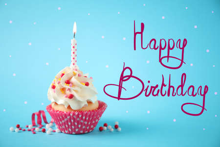 Text Happy Birthday and delicious cupcake with candle on light blue background