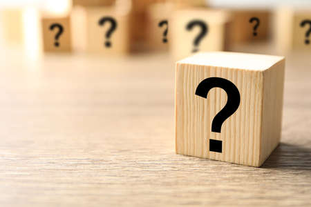 Cube with question mark on wooden background, closeup. Space for text