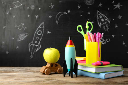 Bright toy rocket, car and school supplies on wooden table Standard-Bild - 143298194