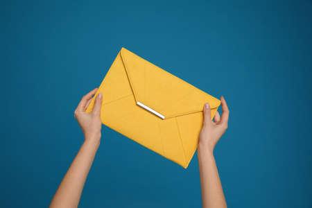 Woman holding stylish envelope bag on blue background, closeup Banque d'images