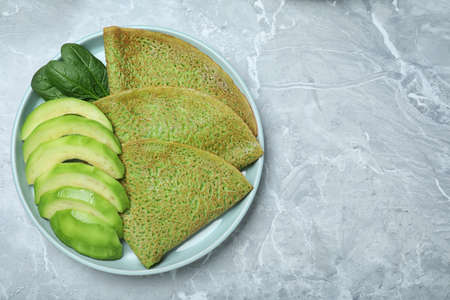 Delicious spinach crepes with avocado on marble table, top view. Space for text